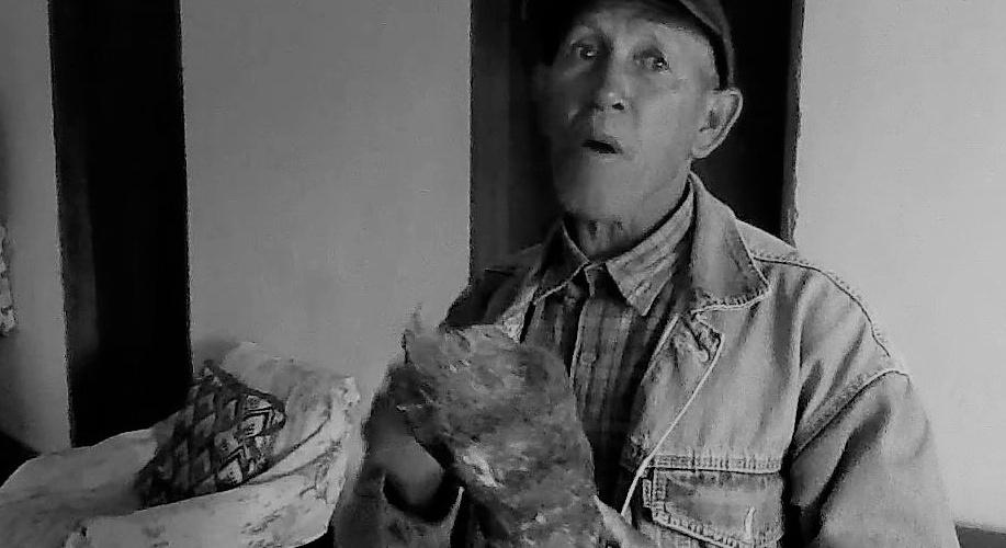 Seu Manuel mostra o tronco da candombá e diz que este pedaço queima por até três horas. Reprodução do vídeo de Helenita Monte de Hollanda