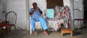 Maria, cujo orixá é Oxóssi, sentada no terreiro. Foto: Paulo Oliveira