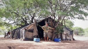 """Bosco mostra a cabana que chama de """"apê"""". Ao fundo a moto que comprou com dinheiro da pesca. Foto: Paulo Oliveira"""