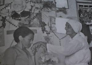 """Mulher pede bênção à Madrinha Dodô. Foto: Do livro """"Madrinha Dodô 20 anos de Saudades"""""""